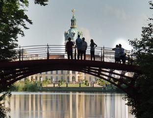 Eine Gruppe steht auf einer Fußgängerbrücke vor einem Schloss.