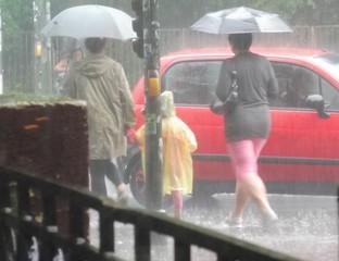 Drei Menschen gehen bei Starkregen mit ihren Schirmen über die Straße.