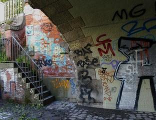 Buntes Graffiti an sden Wänden einer Untertunnelung.