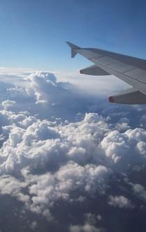 Wolken unter dem Tragflügel eines Flugzeuges.