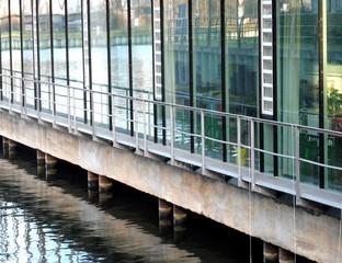 In einer Glasfassade spiegelt sich das Flusswasser.