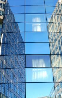 Hinter einer Glasfassade, in der sich umliegende Gebäude spiegeln bauschen sich Vorhänge an offenen Fenstern.