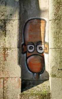 Ein Grafitti zeigt ein schmales Gesicht mit herabgezogenen Mundwinkeln.