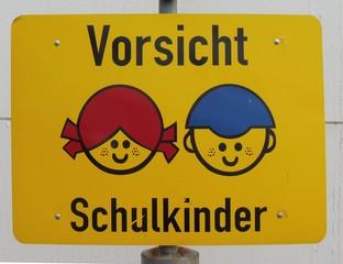Ein buntes Schild zeigt zwei Kindergesichter und den Text: Vorsicht Schulkinder.