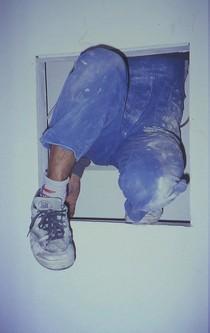Mann im Blaumann klettert aus einem engen Schacht.