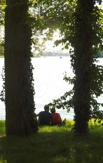 Zwischen zwei Bäumen sitzt ein Paar und schaut über den See.