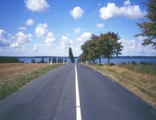 Eine Strasse führt über einen Hügel zum Meer.