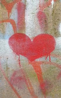 Ein an die Wand gesprühtes Herz von bunten Mustern umgeben.