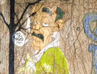 Ein Grafitti zeigt einen Kahlkopf mit Sprechblase.