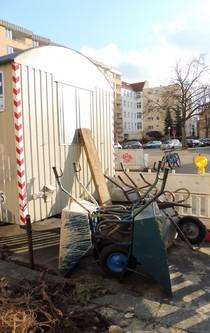 Vor einem Bauwagen stehen mehrere Schubkarren.
