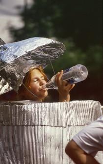 Eine Frau in einer Verkleidung als Tonne trinkt durstig aus einer Flasche.