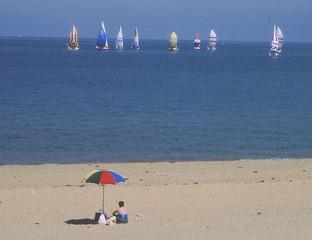 Eine Frau im Badeanzug sitzt neben einem Sonnenschirm am Strand und sieht einer Regatta zu.