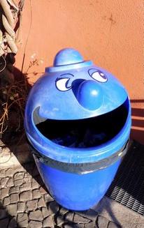 Ein blauer Mülleimer mit Nase und lachenden Augen, dessen Klappe wie ein breit geöffneter Mund aussieht.