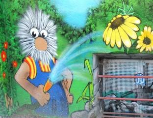 Grafitti an einer Hauswand zeigt Gärtner mit vielen Haaren beim Bumen gießen.