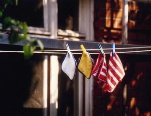 Vier bunte Topflappen hängen an einer Wäscheleine.