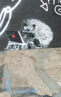 Auf einem Grafitti ist ein Igel an einem Laptop zu sehen.