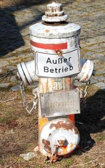 """Ein alter Hydrant mit dem Schild """"Außer Betrieb""""."""