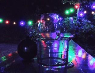 Leere Weingläser nachts auf einem Tisch von Lampions beleuchtet.