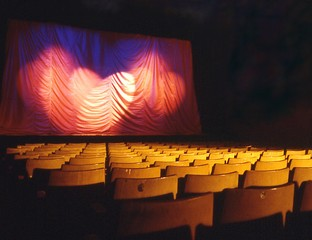 Blick über Stuhlreihen auf eine Theaterbühne.