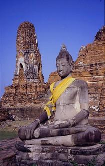 Eine sitzende Buddhastatue in einer alten Tempelanlage.