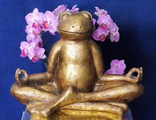 Eine goldene Froschfigur sitzt in Meditationshaltung vor einer Orchidee.
