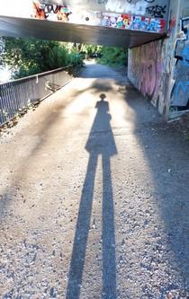 Sehr langer Schatten einer Frau unter einer Brücke.