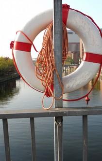 Ein Rettungsring an einer Stange über einem Fluss.
