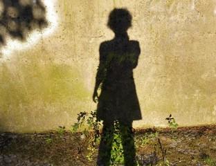 Schatten einer Frau an einer Wand am Abend.